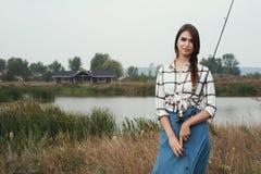 κυρία χωρών που στέκεται ενάντια στη λίμνη στο αγρόκτημα με την ψάρι-ράβδο Στοκ Εικόνες