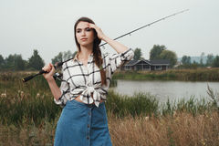 κυρία χωρών που στέκεται ενάντια στη λίμνη στο αγρόκτημα με την ψάρι-ράβδο Στοκ εικόνα με δικαίωμα ελεύθερης χρήσης