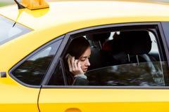Κυρία Brunette στο κλασικό κίτρινο αμάξι που μιλά στο κινητό τηλέφωνο Στοκ Φωτογραφία