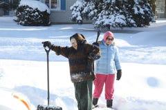 Κυρίες που φτυαρίζουν το χιόνι στοκ εικόνες