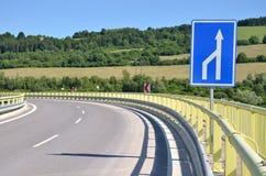 Κυρτός δρόμος τροφοδοτών στην επαρχία, άσπρο σημάδι κυκλοφορίας βελών στο πρώτο πλάνο Στοκ Φωτογραφία