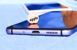 Κυψελοειδές τηλέφωνο Ένα μήλο, ένα παιχνίδι με μια επιγραφή Κινηματογράφηση σε πρώτο πλάνο Στοκ Εικόνες