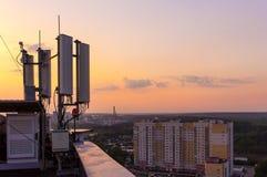 Κυψελοειδής πύργος επικοινωνιών σε ένα υπόβαθρο της πόλης και ένα όμορφο ηλιοβασίλεμα το καλοκαίρι Στοκ Φωτογραφίες