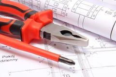 Κυλημένα ηλεκτρικά διαγράμματα και εργαλεία εργασίας στο κατασκευαστικό σχέδιο του σπιτιού Στοκ Φωτογραφίες