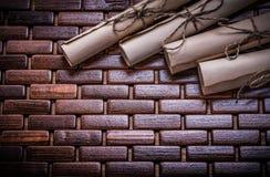 Κυλημένη επάνω παλαιά περγαμηνή στο ψάθινο ξύλινο χαλί Στοκ Εικόνα