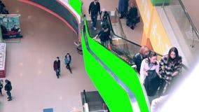 Κυλιόμενη σκάλα στο εσωτερικό λεωφόρων αγορών με τον πράσινο χώρο διαφήμισης οθόνης Τεράστιο εμπορικό κέντρο με το κλειδί χρώματο απόθεμα βίντεο
