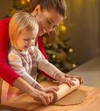 Κυλώντας ζύμη καρφιτσών μητέρων και μωρών διακοσμημένη στη Χριστούγεννα κουζίνα Στοκ Φωτογραφία