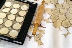 Κυλώντας καρφίτσα με τη ζύμη στον πίνακα κουζινών Προετοιμασία της ζύμης γύρω από το τ Στοκ Εικόνες