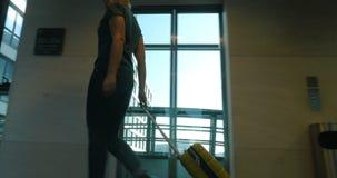 Κυλώντας τσάντα ταξιδιού γυναικών στην αίθουσα ξενοδοχείων απόθεμα βίντεο