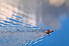 Κωπηλασία σε μια ήρεμη λίμνη Στοκ Φωτογραφία