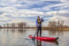 Κωπηλατώντας τη διογκώσιμη στάση paddleboard επάνω στοκ εικόνα με δικαίωμα ελεύθερης χρήσης