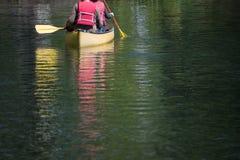 Κωπηλασία σε κανό στην πράσινη λίμνη Στοκ Φωτογραφίες