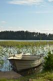Κωπηλασία της βάρκας σε μια ήρεμη λίμνη Στοκ Εικόνα