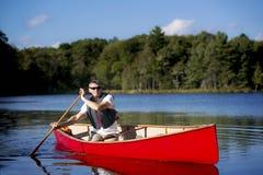 Κωπηλατώντας ένα κόκκινο κανό - Καναδάς Στοκ Εικόνες