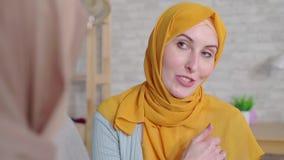 Κωφές νέες μουσουλμανικές γυναίκες προσώπου πορτρέτου όμορφες χαμογελώντας στα hijabs που μιλούν με τη γλώσσα σημαδιών στο καθιστ απόθεμα βίντεο