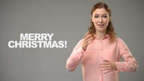 Κωφή κυρία που λέει τη Χαρούμενα Χριστούγεννα στη γλώσσα σημαδιών, κείμενο στο υπόβαθρο, κώφωση απόθεμα βίντεο