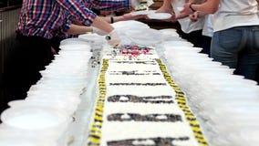Κόβοντας ένα μεγάλο κέικ, εργαζόμενοι, οι ζαχαροπλάστες διαδίδουν ένα τεράστιο κέικ στα πλαστικά πιάτα, απόθεμα βίντεο