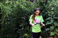 Κόβοντας χορτοτάπητας εφήβων που περιβάλλεται από το δέντρο μηλιάς στοκ εικόνες