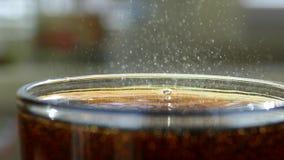 Κόκα κόλα που χύνεται σε ένα γυαλί Όμορφο άλμα φυσαλίδων σε ένα γλυκό ποτό φιλμ μικρού μήκους