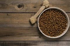 Κόκκαλο σκυλιών και τρόφιμα σκυλιών στον ξύλινο πίνακα Στοκ Εικόνες
