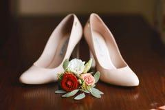 Κόκκινα, άσπρα και ρόδινα λουλούδια ανθοδεσμών γαμήλιων εξαρτημάτων για το νεόνυμφο και μπεζ παπούτσια στο σκοτεινό ξύλινο υπόβαθ Στοκ φωτογραφίες με δικαίωμα ελεύθερης χρήσης