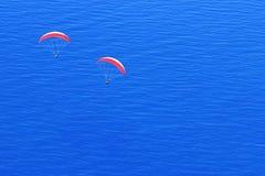 Κόκκινα αλεξίπτωτα στον ουρανό επάνω από την μπλε θάλασσα Εικόνα στο ύφος του μινιμαλισμού Στοκ φωτογραφίες με δικαίωμα ελεύθερης χρήσης