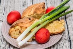 Κόκκινα αυγά Πάσχας με το κρεμμύδι άνοιξη και το γλυκό ψωμί Istrian Πάσχα Στοκ Φωτογραφία