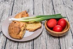 Κόκκινα αυγά Πάσχας σε ένα κύπελλο με το κρεμμύδι άνοιξη Στοκ Φωτογραφία