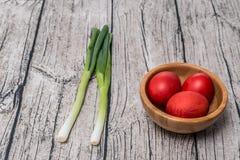 Κόκκινα αυγά Πάσχας σε ένα κύπελλο με το κρεμμύδι άνοιξη Στοκ Εικόνες