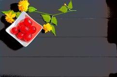 Κόκκινα αυγά Πάσχας σοκολάτας και κίτρινα λουλούδια με το σκοτεινό ξύλινο υπόβαθρο στοκ φωτογραφίες
