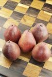 Κόκκινα αχλάδια σε έναν ξύλινο πίνακα σκακιού Στοκ Εικόνες