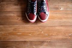 Κόκκινα γαμήλια πάνινα παπούτσια στο καφετί πάτωμα Στοκ Εικόνα