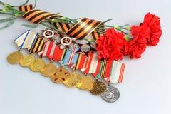 Κόκκινα γαρίφαλα που δένονται με την κορδέλλα Αγίου George, μετάλλια, διαταγές Στοκ Φωτογραφία