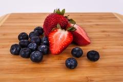 Κόκκινα γλυκά οργανικά βακκίνια φραουλών μούρων σε έναν τέμνοντα cuttingboard στοκ εικόνες