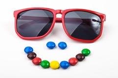 Κόκκινα γυαλιά ηλίου και ζωηρόχρωμα candys Στοκ Εικόνες