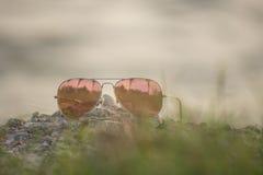 Κόκκινα γυαλιά ηλίου στο βράχο, γυαλιά ηλίου εστίασης Στοκ Φωτογραφίες