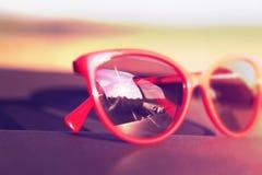 Κόκκινα γυαλιά ηλίου στο ταμπλό αυτοκινήτων με την αντανάκλαση του ήλιου Στοκ Εικόνες