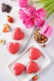 Κόκκινα διαμορφωμένα καρδιά mousse κέικ με τα μούρα και τη σοκολάτα στοκ εικόνα