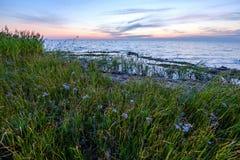 Κόκκινα διαποτισμένα χρώματα στο ηλιοβασίλεμα πέρα από τη θάλασσα της Βαλτικής με το ήρεμες νερό και τις αντανακλάσεις ήλιων στην στοκ εικόνες