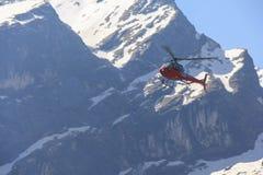 Κόκκινα ελικόπτερο και βουνό του Ιμαλαίαυ Annapurna, Νεπάλ Στοκ φωτογραφία με δικαίωμα ελεύθερης χρήσης