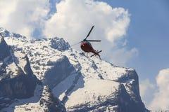 Κόκκινα ελικόπτερο και βουνό του Ιμαλαίαυ Annapurna, Νεπάλ Στοκ Εικόνες