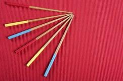Κόκκινα, κίτρινα και μπλε chopsticks aqua στον κόκκινο πίνακα χαλιών τοποθετούν τη ρύθμιση Στοκ φωτογραφίες με δικαίωμα ελεύθερης χρήσης
