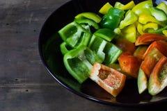 Κόκκινα, κίτρινα και πιπέρια κουδουνιών που τεμαχίζονται στο μαύρο πιάτο Στοκ εικόνες με δικαίωμα ελεύθερης χρήσης