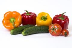 Κόκκινα κίτρινα και πορτοκαλιά πιπέρια με τις ντομάτες σε ένα άσπρο υπόβαθρο Αγγούρια με τα ζωηρόχρωμα πιπέρια στη σύνθεση σε ένα Στοκ Εικόνες