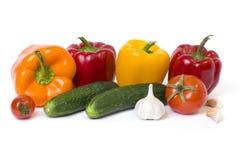 Κόκκινα κίτρινα και πορτοκαλιά πιπέρια με τις ντομάτες σε ένα άσπρο υπόβαθρο Αγγούρια με τα ζωηρόχρωμα πιπέρια στη σύνθεση σε ένα Στοκ φωτογραφία με δικαίωμα ελεύθερης χρήσης