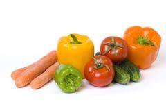 Κόκκινα κίτρινα και πορτοκαλιά πιπέρια με τις ντομάτες σε ένα άσπρο υπόβαθρο Αγγούρια με τα ζωηρόχρωμα πιπέρια στη σύνθεση σε ένα Στοκ εικόνα με δικαίωμα ελεύθερης χρήσης