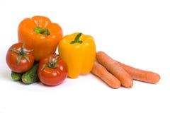 Κόκκινα κίτρινα και πορτοκαλιά πιπέρια με τις ντομάτες σε ένα άσπρο υπόβαθρο Αγγούρια με τα ζωηρόχρωμα πιπέρια στη σύνθεση σε ένα Στοκ εικόνες με δικαίωμα ελεύθερης χρήσης