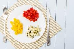 Κόκκινα, κίτρινα πιπέρια κουδουνιών και egplant στο άσπρο πιάτο Λεπτά - τεμαχισμένος ingridients για τα υγιή τρόφιμα διάστημα αντ Στοκ Φωτογραφία