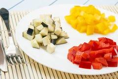 Κόκκινα, κίτρινα πιπέρια κουδουνιών και egplant στο άσπρο πιάτο Λεπτά - τεμαχισμένος ingridients για τα υγιή τρόφιμα Οργανικά προ Στοκ φωτογραφία με δικαίωμα ελεύθερης χρήσης