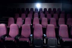 κόκκινα καθίσματα στην κενή σκοτεινή κινηματογραφική αίθουσα Στοκ Φωτογραφία